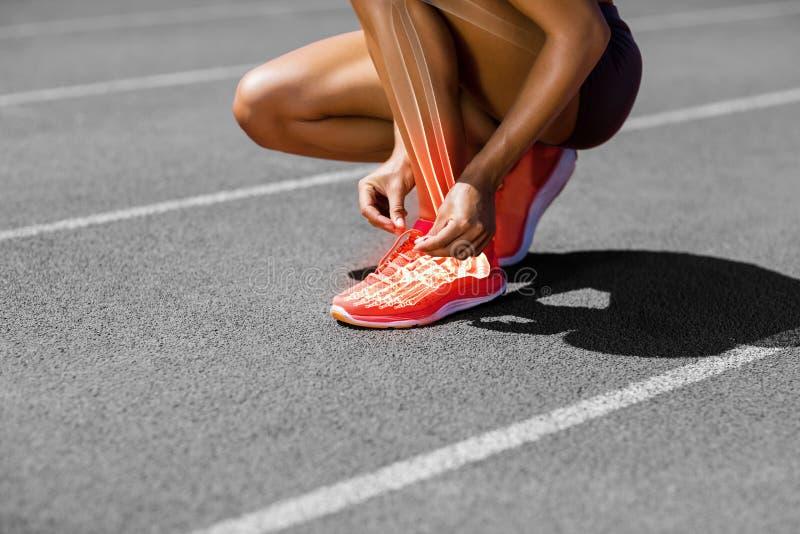 Sezione bassa della sportiva che lega laccetto sulla pista immagine stock