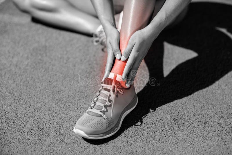Sezione bassa della sportiva che soffre dai dolori articolari sulla pista immagine stock libera da diritti