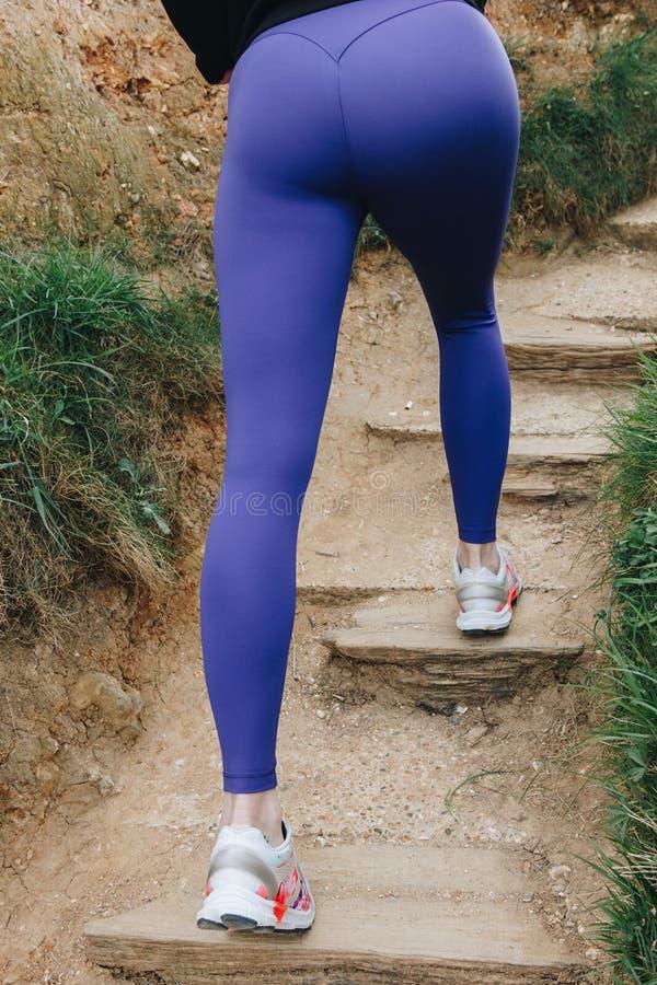 sezione bassa della sportiva in scarpe da tennis correnti su sulle scale, immagini stock libere da diritti