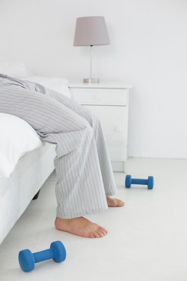 Sezione bassa di un giovane in pigiama che si trova a letto fotografie stock libere da diritti
