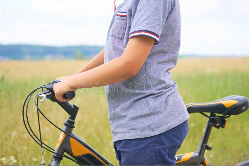 Sezione centrale dell'adolescente che tiene il manubrio di una bicicletta e dei giri lungo la strada accanto al campo fotografie stock libere da diritti