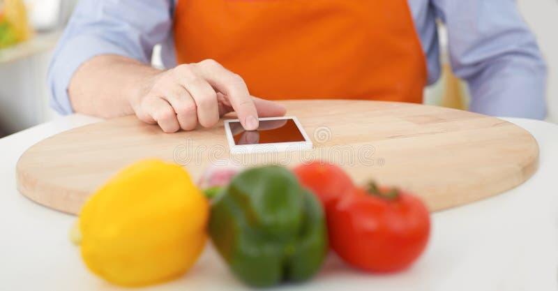 Sezione centrale di un uomo maturo che indica dito lo smartphone sul tagliere Cottura, tecnologia e concetto domestico fotografia stock