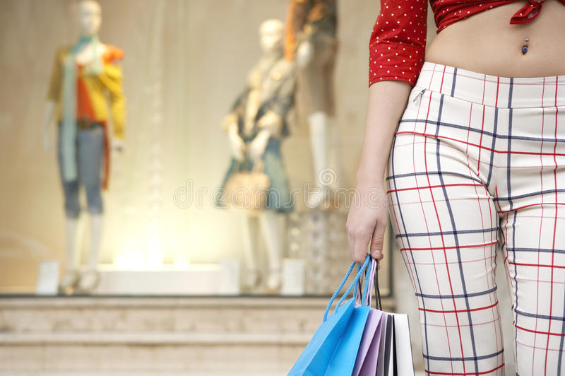 Sezione della donna che si leva in piedi con i sacchetti di acquisto immagini stock