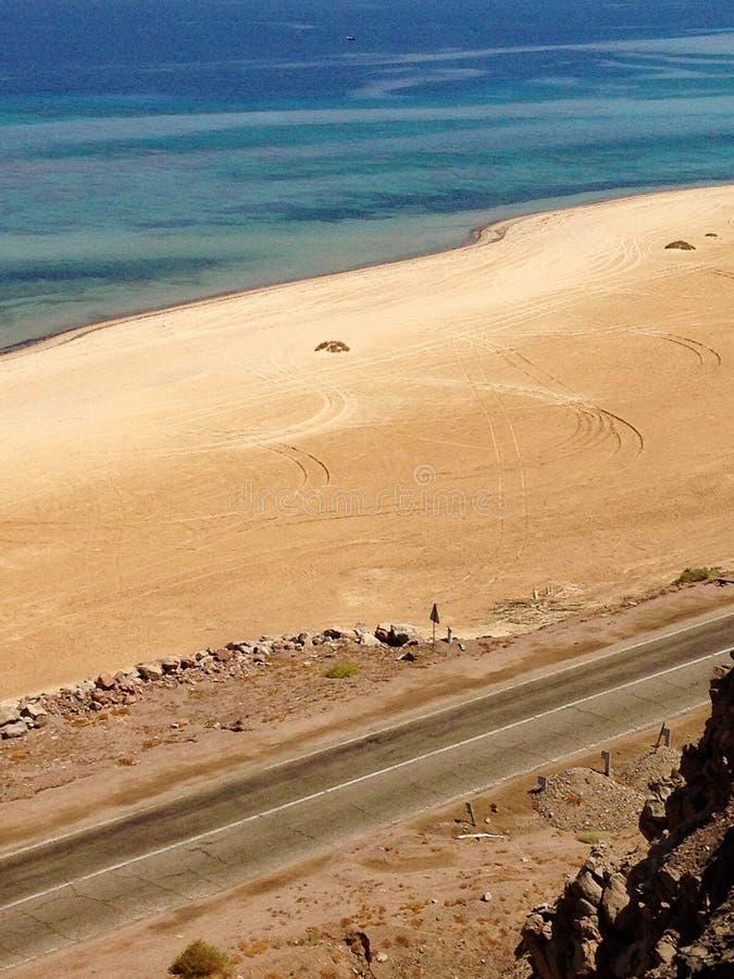 Sezione della strada accanto alla spiaggia e dell'oceano nell'Egitto fotografie stock