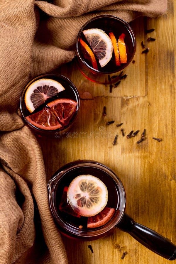 Sezonowy i wakacje pojęcia boże narodzenie rozmyślający wino z pięknymi pomarańcze plasterkami wśrodku szkła, zakrywającego z cie zdjęcia royalty free