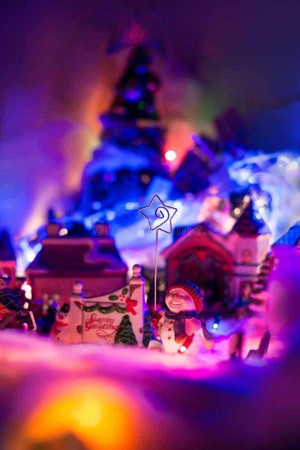 Sezonu powitania znak z uśmiechniętą bałwanu mienia gwiazdą Bethlehem stojaki przed boże narodzenie wioską Bajki świąteczna minut fotografia royalty free