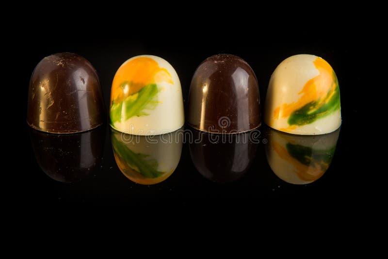 Sfären för Closeup fyra formade godisar bildar vit och svart choklad arkivbilder