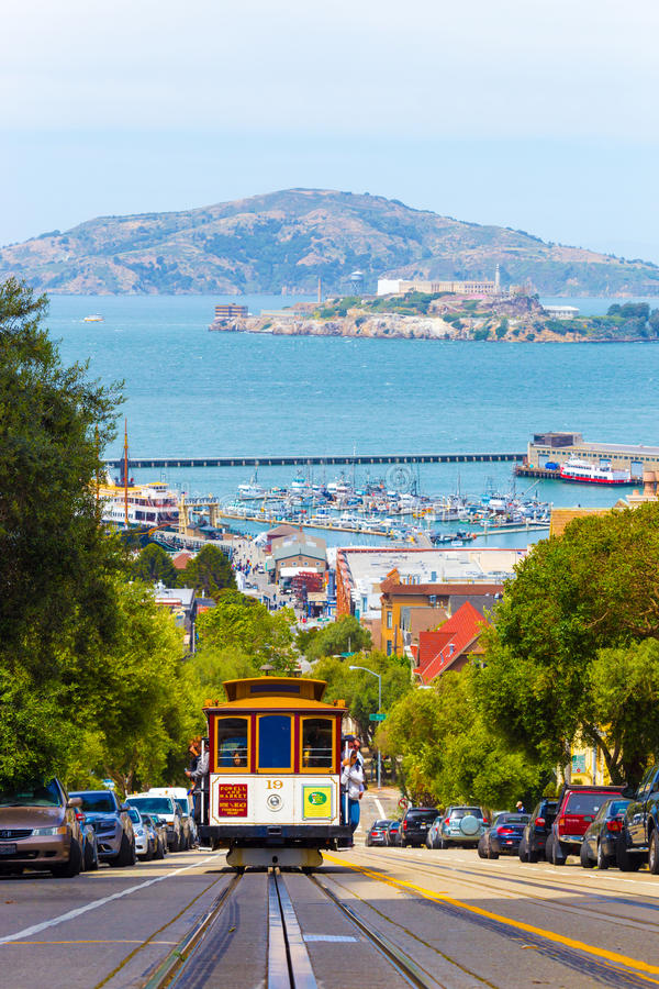 SF Cable Car Coming Uphill Alcatraz Angel Island. San Francisco, USA - May 19, 2016: Approaching cable car full of tourists coming uphill with Angel and Alcatraz stock images