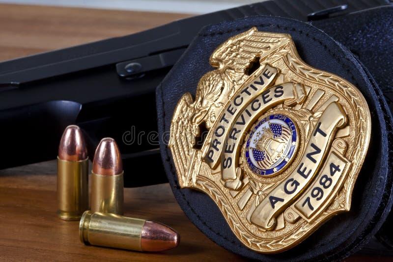 Sfałszowana odznaka robić fotografem z pistolecikiem na drewnie i pociski, obraz stock