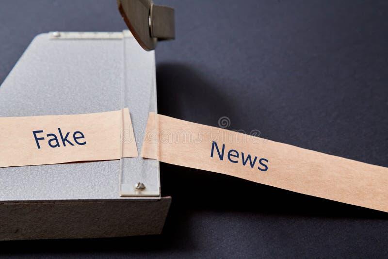 Sfałszowana wiadomość, dezinformacja, fałszywa informacja lub propagandy pojęcie, Krajacz i Kraft papier zdjęcie stock