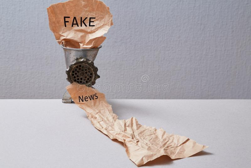 Sfałszowana wiadomość, dezinformacja, fałszywa informacja lub propagandy pojęcie, Maszynka do mięsa i miący papier zdjęcia royalty free