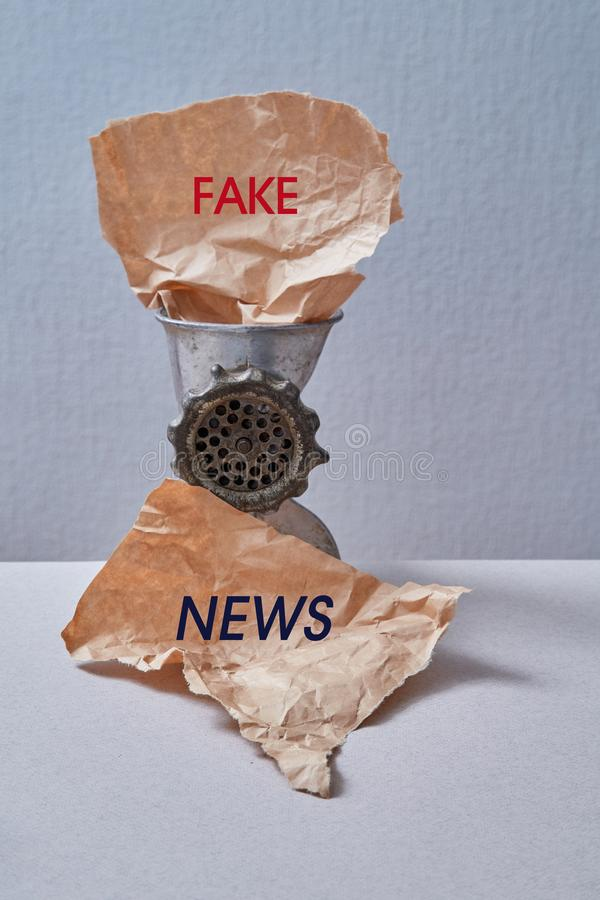 Sfałszowana wiadomość, dezinformacja, fałszywa informacja lub propagandy pojęcie, Maszynka do mięsa i miący papier fotografia stock