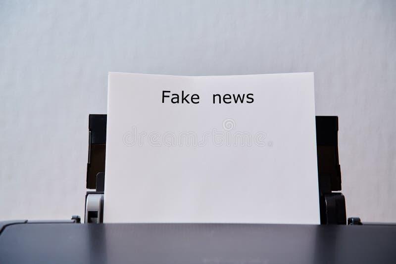 Sfałszowana wiadomość, dezinformacja, fałszywa informacja lub propagandy pojęcie, Prześcieradło z inskrypcją w drukarce obraz stock