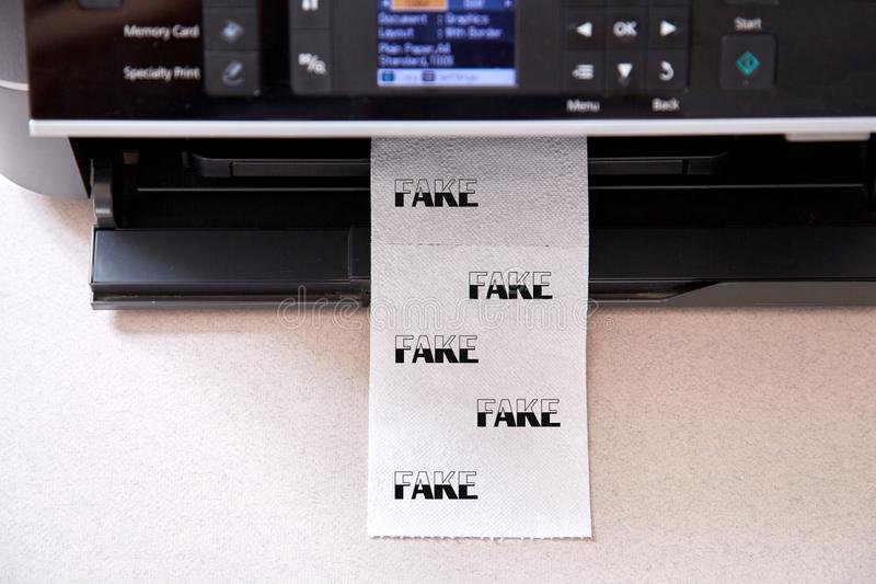 Sfałszowana wiadomość, dezinformacja, fałszywa informacja lub propagandy pojęcie, Rolka papier toaletowy i drukarka, zdjęcie stock