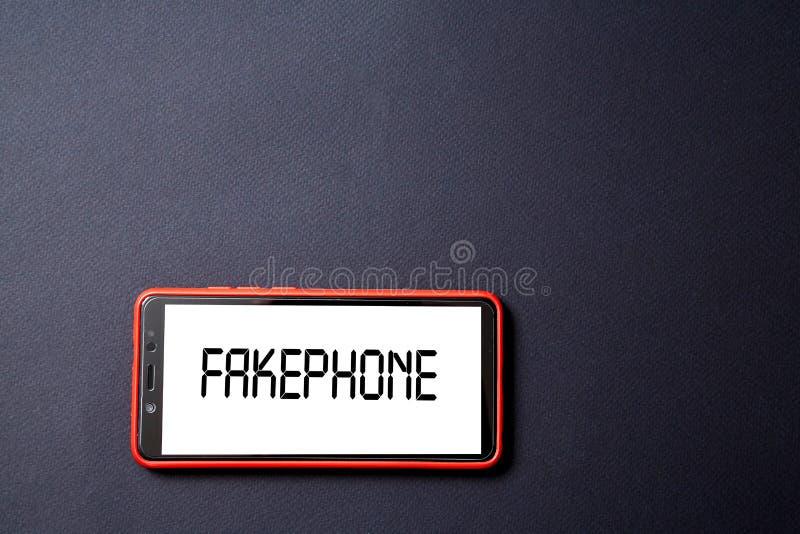Sfałszowana wiadomość, dezinformacja, fałszywa informacja lub propagandy pojęcie, Smartphone i inskrypcja na czarnym tle obrazy stock