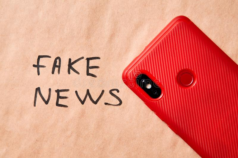 Sfałszowana wiadomość, dezinformacja, fałszywa informacja lub propagandy pojęcie, Telefon w tle z inskrypcją zdjęcia royalty free