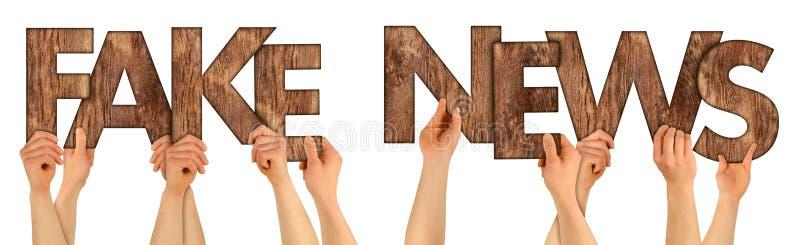 SFAŁSZOWANI wiadomości ludzie trzyma up brown nieociosanego dębowego drewnianego listu isol zdjęcie royalty free