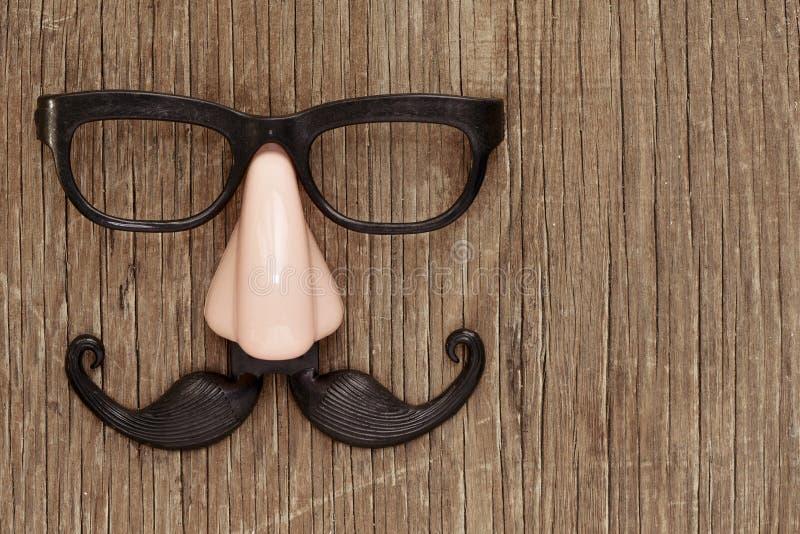 Sfałszowany wąsy, nos i eyeglasses na drewnianej powierzchni, zdjęcie stock