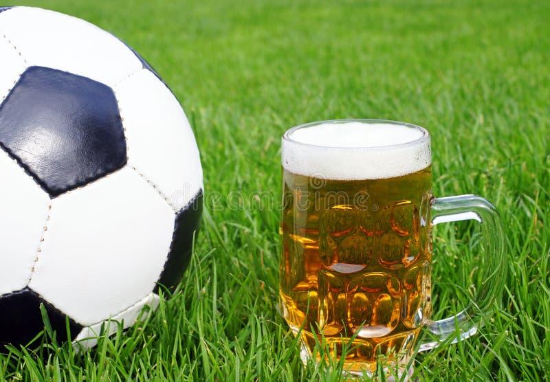 Sfera di calcio con la tazza di birra fotografia stock