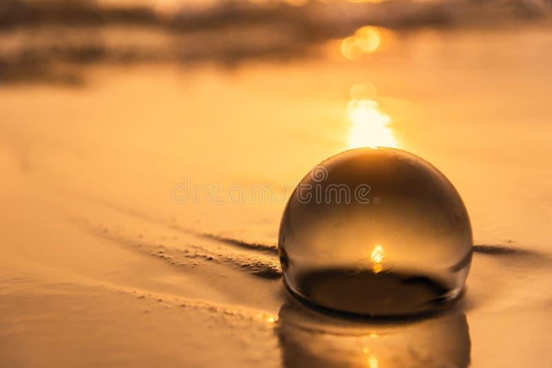 Sfera di cristallo sulla spiaggia con le onde del mare ad alba di mattina thailand immagini stock