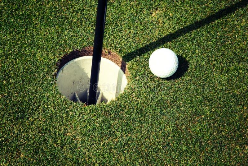 Sfera di golf al foro immagini stock