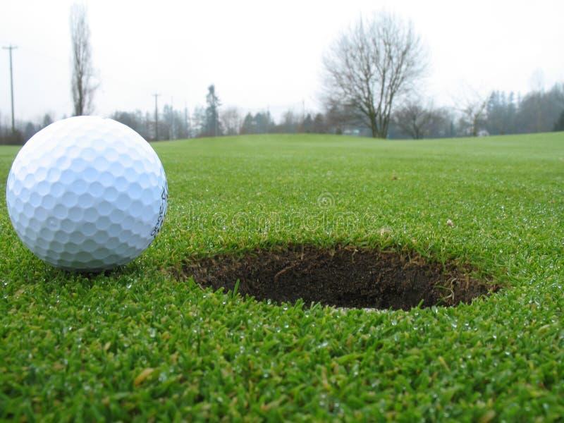 Sfera di golf al lato del foro fotografia stock