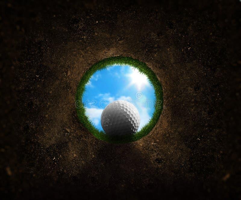 Sfera di golf che cade nella tazza fotografia stock