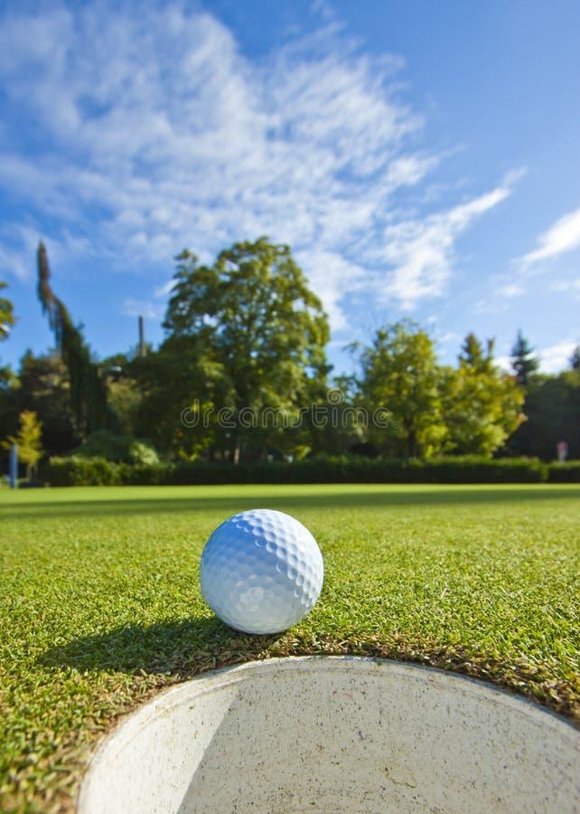 Sfera di golf prima della tazza immagine stock