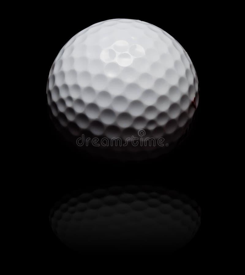 Sfera di golf in punto sul nero immagine stock