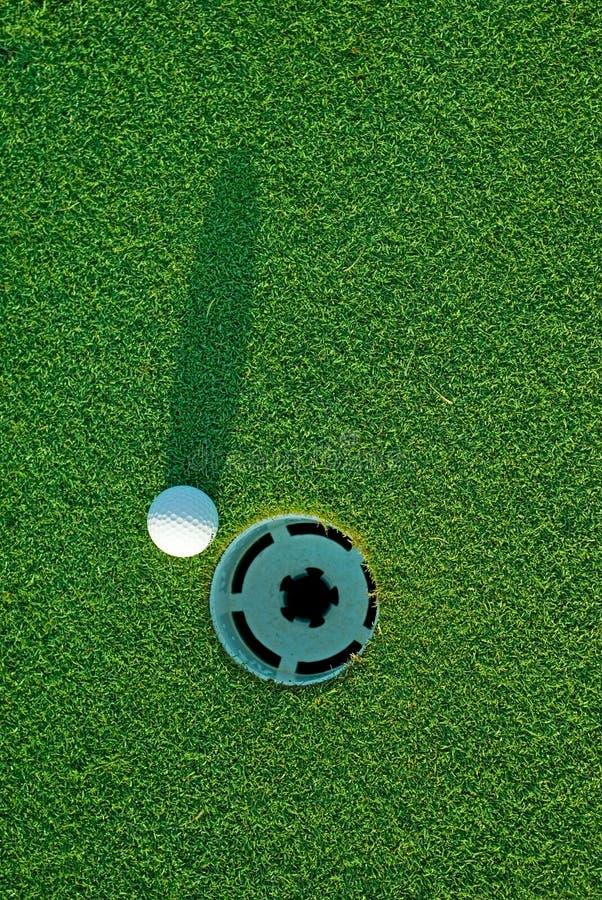 Sfera di golf sopra vicino al foro 3 fotografie stock libere da diritti