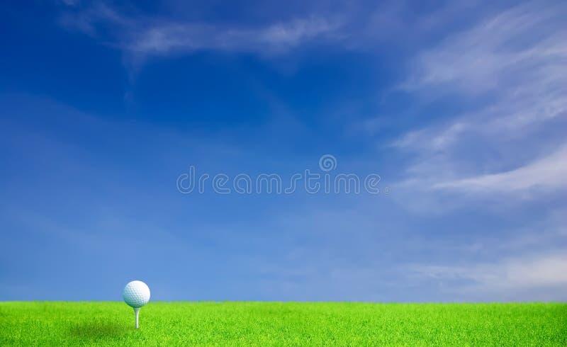Sfera di golf su erba sotto cielo blu fotografia stock