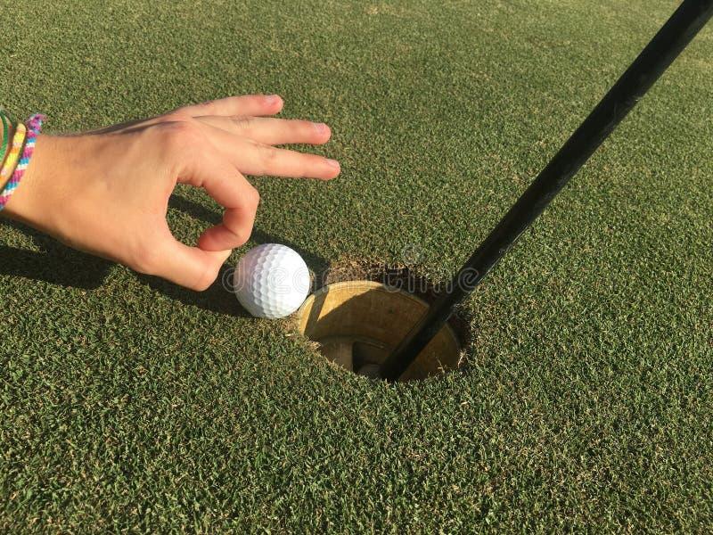 Sfera di golf sul bordo del foro fotografie stock