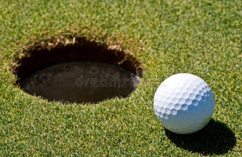 Sfera di golf vicino ad un foro immagine stock libera da diritti