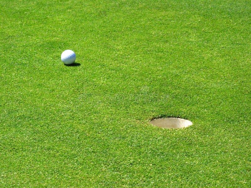 Sfera di golf vicino al foro fotografie stock