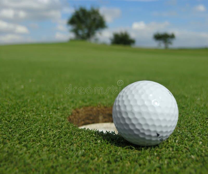 Sfera di golf vicino al foro fotografia stock