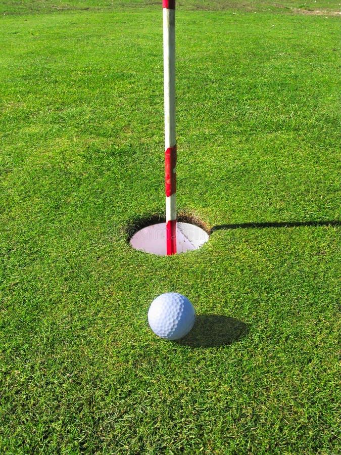 Sfera di golf vicino al foro. fotografia stock libera da diritti