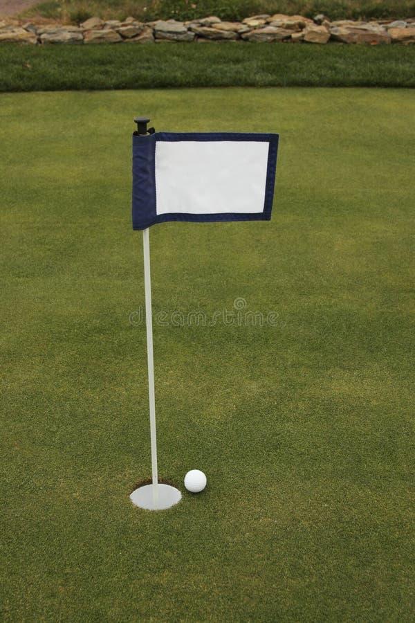Sfera di golf vicino alla bandierina vicina di verde mettente del foro fotografie stock libere da diritti