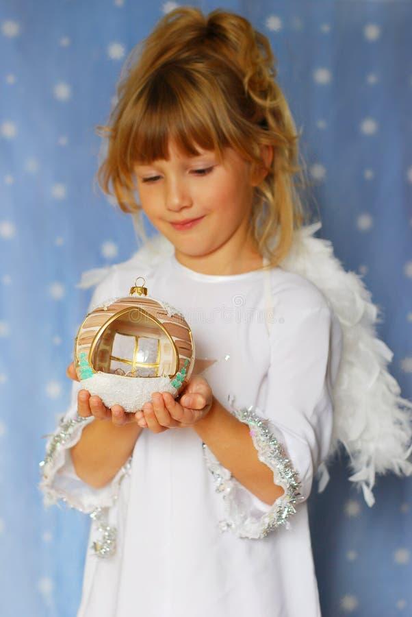 Sfera di natale della holding della ragazza di angelo a disposizione immagini stock