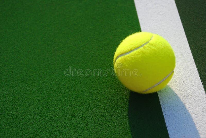 Sfera di tennis gialla sulla riga laterale bianca fotografia stock