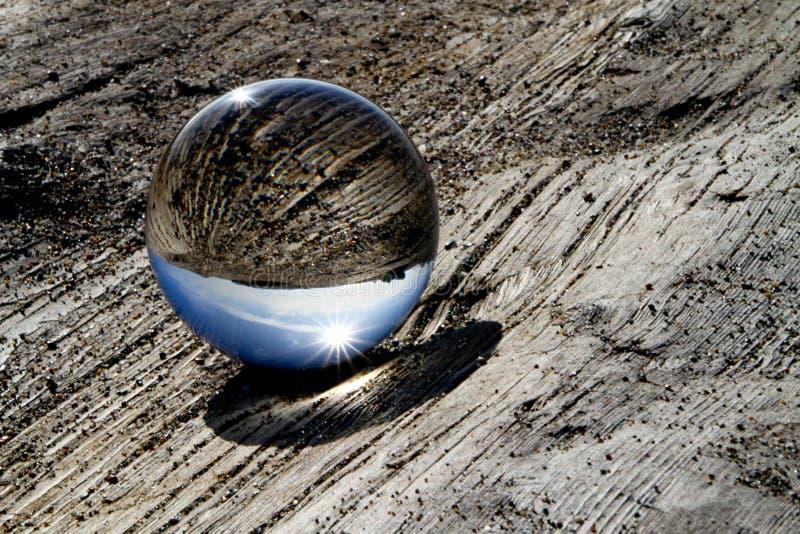 Sfera di vetro su Driftwood fotografie stock