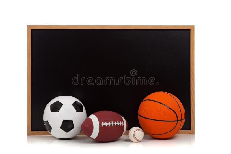 Sfere Assorted di sport con una priorità bassa della lavagna fotografia stock