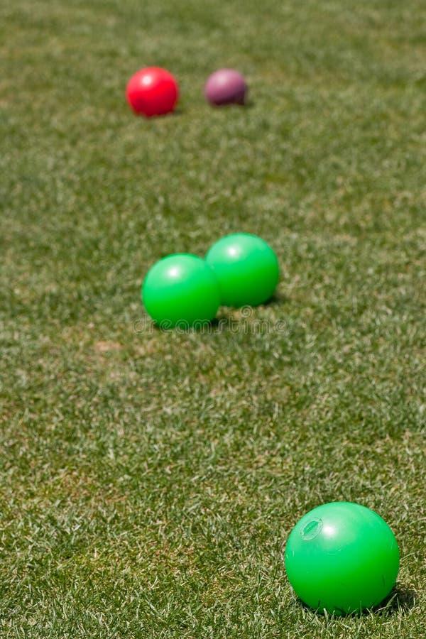 Sfere di Bocce variopinte in erba verde fotografie stock