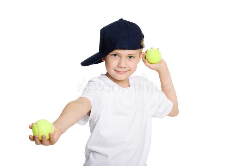 Sfere di tennis di lancio del ragazzo fotografia stock