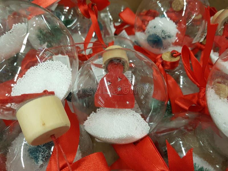 Sfere di vetro trasparenti con neve artificiale e le figure rosse di un cappuccio fotografia stock