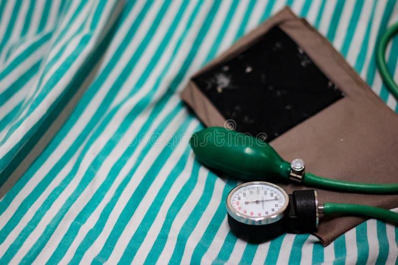 Sfigmomanometro della macchina di pressione sanguigna sul letto con il polsino ed involucro e tubatura del braccio immagini stock libere da diritti