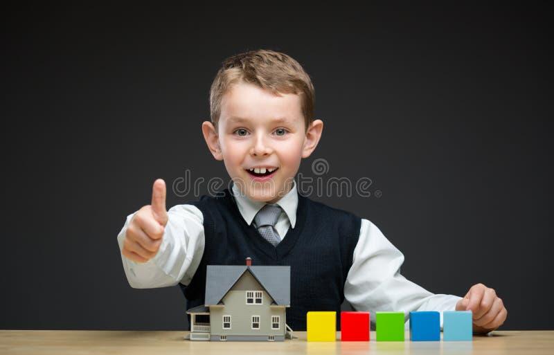 Sfogliando sul ragazzino con il modello ed i blocchetti della casa immagine stock