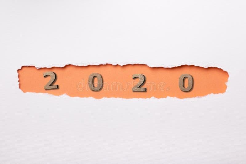 Sfondo bianco con figura in legno della data 2020 nel foro arancione di cartone strappato, concetto di nuovo anno, progetto di co fotografie stock