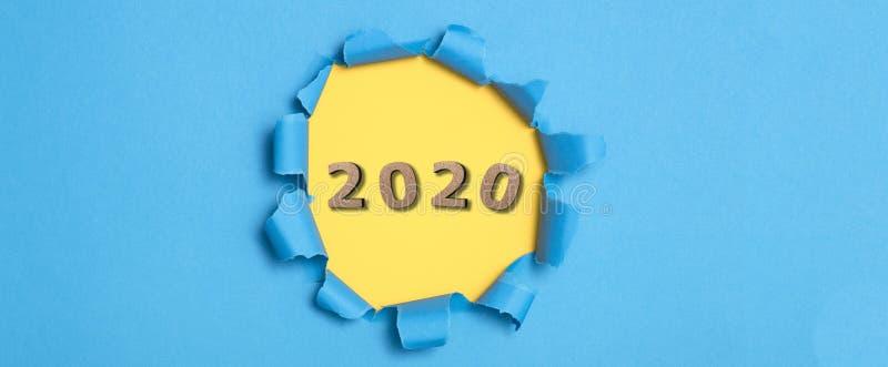 Sfondo colorato con figura in legno della data 2020 in un foro giallo di cartone blu strappato, concetto di nuovo anno, copertura fotografie stock libere da diritti
