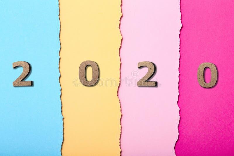 Sfondo con cifre in legno della data 2020 sulle strisce di cartone multicolore, nuovo anno, progetto di copertina del calendario fotografia stock