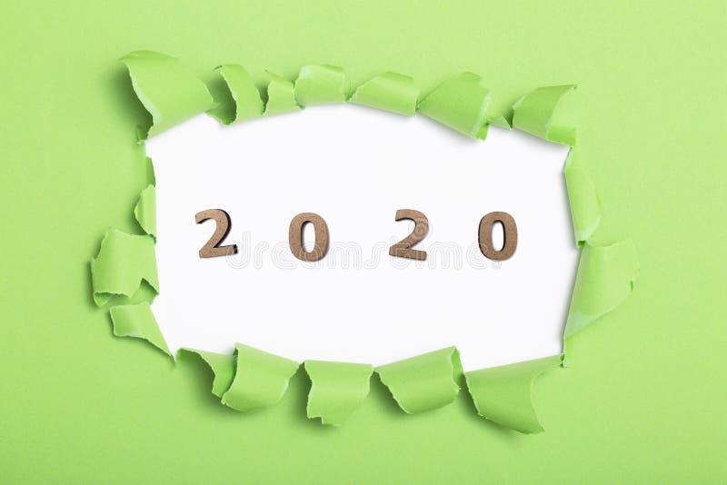 Sfondo di colore verde con figura in legno della data 2020 nel foro verde del cartone strappato, concetto di nuovo anno, copertur fotografie stock